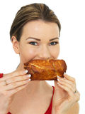 Attractive Young Woman Holding a Cooked Hot Savory Sausage Roll Royalty Free Stock Photos