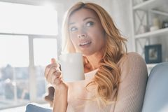 Just inspired. Attractive young woman holding a cup and looking away while spending time at home Royalty Free Stock Photo