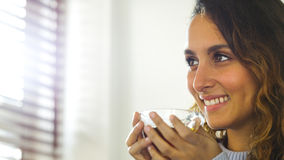 Attractive young woman holding a drink and smiling Stock Photos