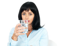 Attractive Young Woman Holding a Glass of Still Clear Water. Attractive Young Woman, with short bobbed black or dark hair, in her twenties, holding a glass of Royalty Free Stock Photos