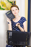 Woman planning shopping budget with calculator. Attractive young woman holding grocery basket planning shopping budget while thinking with a calculator to head Royalty Free Stock Photos