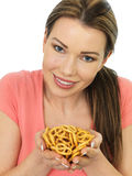 Attractive Young Woman Holding A Handful Of Salted Pretzels Stock Image