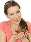 Attractive Young woman Holding A Handful Of Savory Twigglets Stock Image