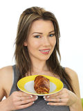 Attractive Young Woman Holding A Large Sausage Roll on a Plate Royalty Free Stock Photos