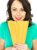 Attractive Young Woman Holding A Line Of Dried Spaghetti Pasta Royalty Free Stock Images