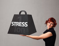 Young woman holding one ton of stress weight. Attractive young woman holding one ton of stress weight Royalty Free Stock Photography