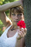 Attractive young woman holding out a red rose Royalty Free Stock Photography