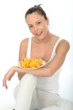 Attractive Young Woman Holding a Plate of Cut Oranges Stock Images