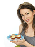 Attractive Young Woman Holding a Plate of Scotch Eggs Royalty Free Stock Photography