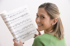 Attractive Young Woman Holding Sheet Music Stock Image