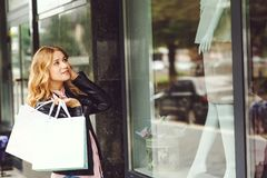 Attractive young woman holding shopping bags while standing in front of shop window. Royalty Free Stock Photo
