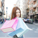 Attractive young woman holding shopping bags in the street. Stock Image