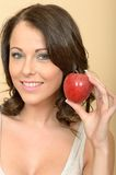 Attractive Young Woman Holding a Single Fresh Ripe Juicy Apple Stock Photo
