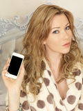 Attractive Young Woman Holding a Smartphone Royalty Free Stock Photo