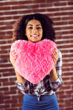 Attractive young woman holding up heart-shaped pillow Royalty Free Stock Images