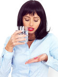 Attractive Young Woman Holing a Glass of Water and Two Tablets Stock Photos