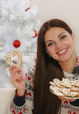 Attractive young woman with home cookies on Christmas tree backg Royalty Free Stock Image