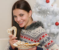 Attractive young woman with home cookies near Christmas tree Royalty Free Stock Photos