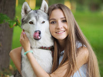 Attractive young woman hugs funny siberian husky dog with brown eyes. Who show its tongue royalty free stock image