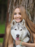 Attractive young woman hugs funny siberian husky dog with brown eyes who show its tongue. In the park stock images