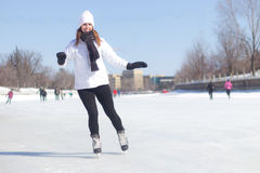Attractive young woman ice skating during winter stock photography