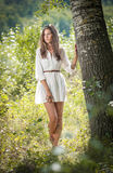 Attractive Young Woman In White Short Dress Posing Near A Tree In A Sunny Summer Day. Beautiful Girl Enjoying The Nature Stock Photos