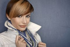 Attractive young woman in jacket and scarf. Over grey background stock photo