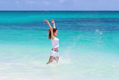 Attractive young woman jumping in the ocean. Attractive young little woman jumping in the ocean Royalty Free Stock Photo