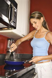 Attractive Young Woman in Kitchen Cooking Stock Photos