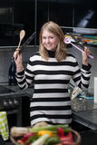 Attractive, young woman with kitchen utensils Royalty Free Stock Photos