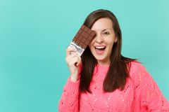 Attractive young woman in knitted pink sweater hold in hand, covering eye with chocolate bar isolated on blue turquoise. Wall background, studio portrait royalty free stock images