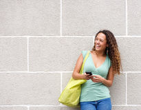 Attractive young woman laughing with mobile phone Royalty Free Stock Photo
