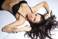 Attractive young woman laying on bed Stock Images