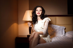 Attractive young woman on bedroom. Attractive young woman laying on bedroom in hotel Royalty Free Stock Image