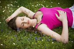 Attractive young woman laying down in grassland Stock Photography