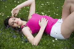 Attractive young woman laying down in grassland, casual dress Royalty Free Stock Photos