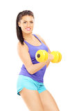 Attractive young woman lifting a dumbbell Stock Photography