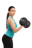 Attractive young woman lifting a dumbbell. And looking at the camera isolated on white background Royalty Free Stock Photos