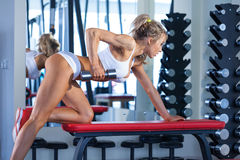 Attractive young woman lifting dumbbells Stock Photo