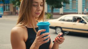 Attractive young woman with light brown hair uses smartphone and drinks coffee in the city center. Attractive young woman with light brown hair and black dress stock footage
