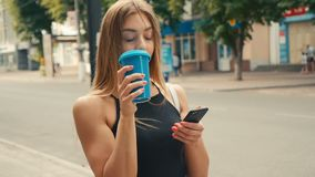 Attractive young woman with light brown hair uses smartphone and drinks coffee in the city center. Attractive young woman with light brown hair and black dress stock video