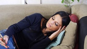 Attractive young woman listening to music on headphones. Eyes closed. Indoor shot in house Royalty Free Stock Photos
