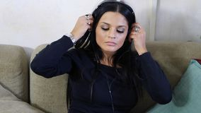 Attractive young woman listening to music on headphones. Eyes closed. Indoor shot in house Royalty Free Stock Images