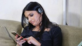 Attractive young woman listening to music on headphones. Eyes closed. Indoor shot in house Stock Photo