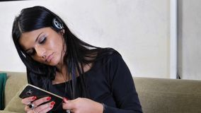 Attractive young woman listening to music on headphones. Eyes closed. Indoor shot in house Stock Photography