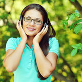 Attractive young woman listening to music with headphones on nat Stock Photo