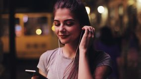 Attractive young woman listening to music on smart phone outdoors in evening. Portrait of smiling girl standing outside stock video