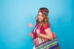 Attractive young woman with lollipop in hand on blue background with copy space Stock Photos