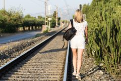 An attractive young woman with long brown hair walking near the railway stock photos