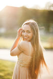 Attractive young woman with long dress enjoying her time outside in park sunset background Royalty Free Stock Photo